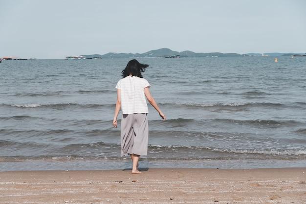 Asiatische frau, die allein am strand geht. konzept für urlaub und entspannung.