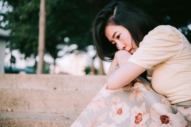 Asiatische frau, die alleine und depressiv sitzt, hört auf, häusliche gewalt und gesundheitsangst zu missbrauchen.