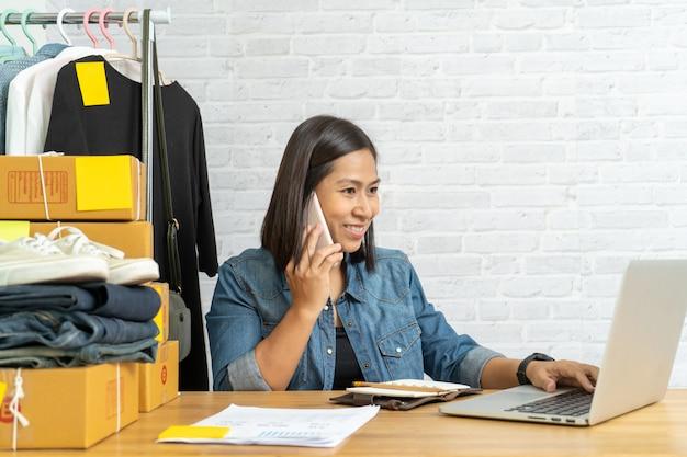 Asiatische frau, die am laptop mit sprechendem smartphone arbeitet und online verkauft
