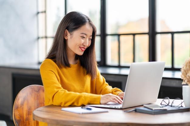 Asiatische frau, die am laptop zu hause oder im café arbeitet. junge dame im leuchtend gelben pullover