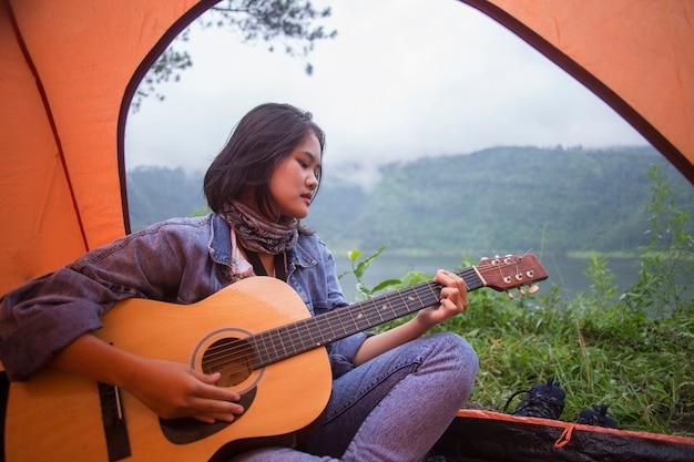 Asiatische frau, die am morgen gitarre in einem zelt spielt