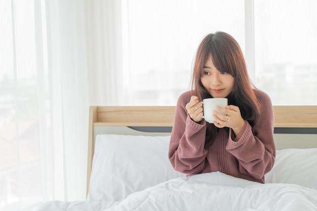 Asiatische frau, die am morgen kaffee auf bett trinkt