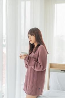 Asiatische frau, die am morgen kaffee trinkt
