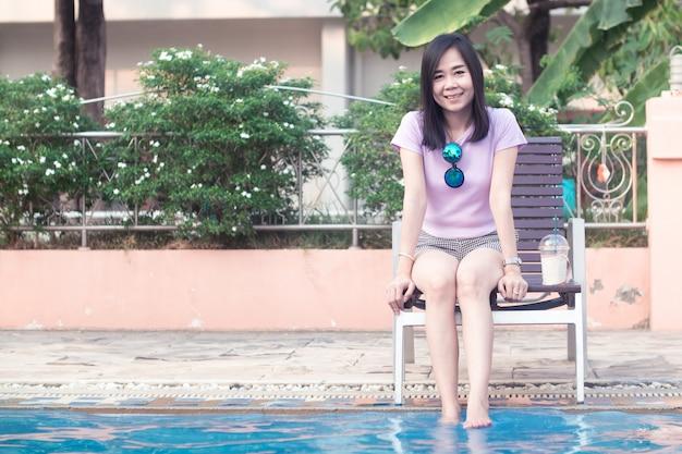 Asiatische frau, die am poolside mit beiden füßen auf dem wasser stillsteht