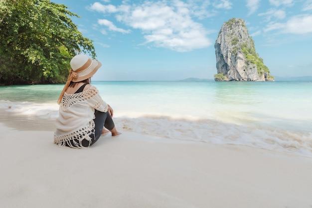 Asiatische frau, die am strand sitzt und das erstaunliche meer betrachtet und mit schöner natur in ihrem urlaub genießt. sommerferienkonzept.