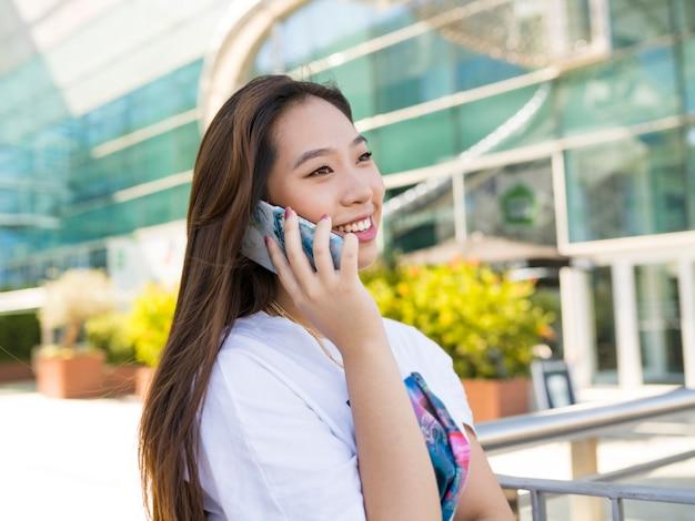 Asiatische frau, die am telefon in der stadt spricht
