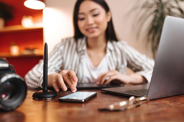Asiatische frau, die am telefon mit lächeln und aufstellen am arbeitsplatz mit grauem laptop plaudert