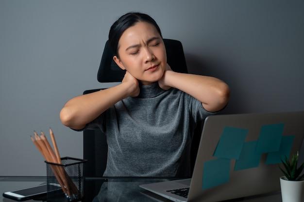 Asiatische frau, die an einem laptop arbeitete, war krank mit körperschmerzen, die im büro saßen