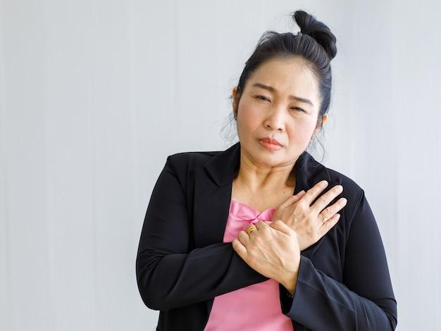 Asiatische frau, die an plötzlichem herzinfarkt leidet und brust hält. konzept der notfallversorgung und betroffen von stauungsversagen oder herz-lungen-wiederbelebung, herzproblemen.