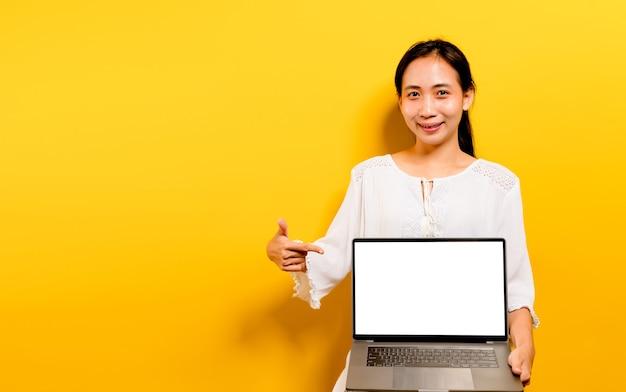 Asiatische frau, die an seinem laptop arbeitet, und ein glückliches lächeln, glückliches arbeitskonzept auf gelbem hintergrund im studio Premium Fotos