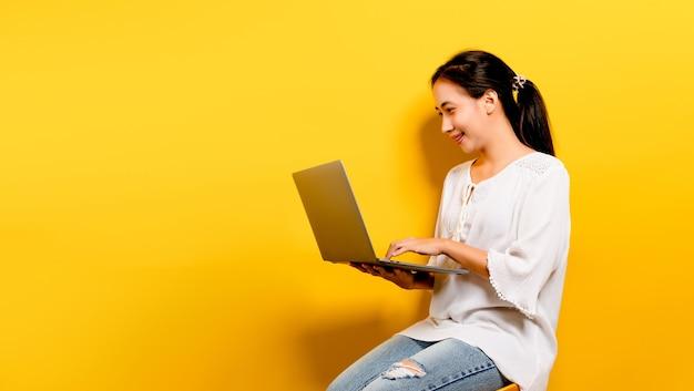 Asiatische frau, die an seinem laptop arbeitet, und ein glückliches lächeln, glückliches arbeitskonzept auf gelbem hintergrund im studio