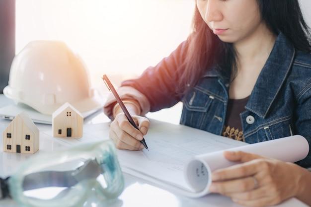 Asiatische frau, die architekturplan mit persönlicher sicherheitsausrüstung und holzhausmodell prüft