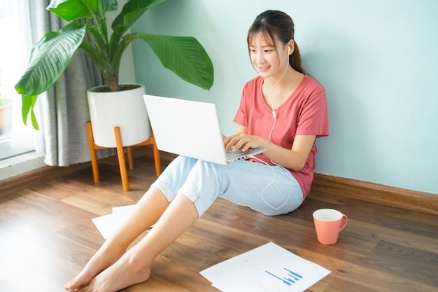 Asiatische frau, die auf dem boden sitzt, während sie von zu hause aus arbeitet