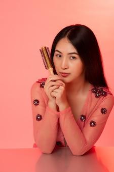 Asiatische frau, die auf dem schreibtisch hält kamm auf rosa hintergrund sitzt