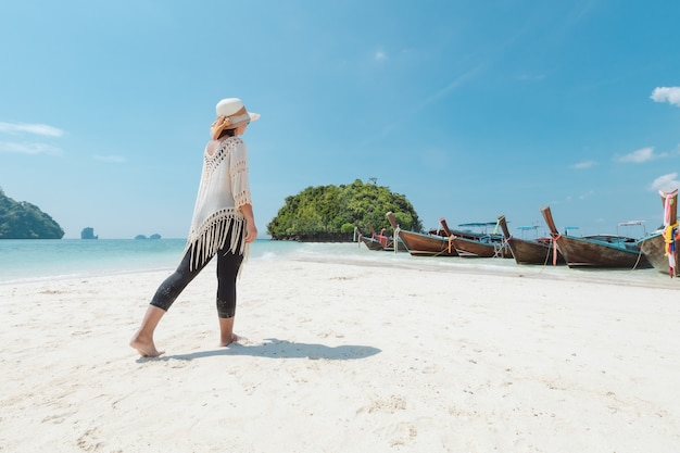 Asiatische frau, die auf dem strand geht und mit schöner natur in ihrem urlaub genießt. sommerferienkonzept.