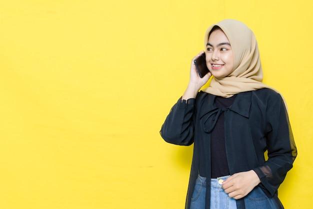 Asiatische frau, die auf einem smartphone spricht