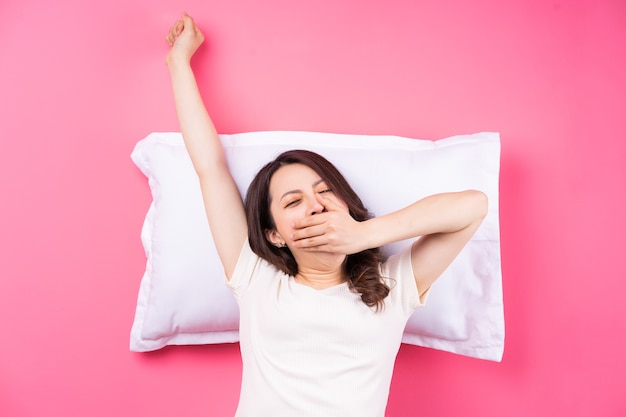 Asiatische frau, die auf rosa schläft