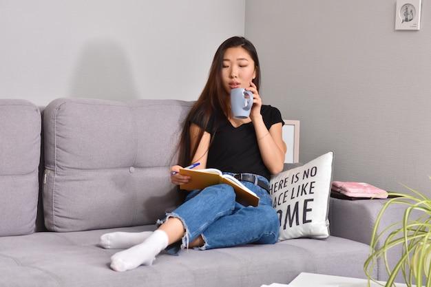 Asiatische frau, die auf sofa und orangeem heft sitzt