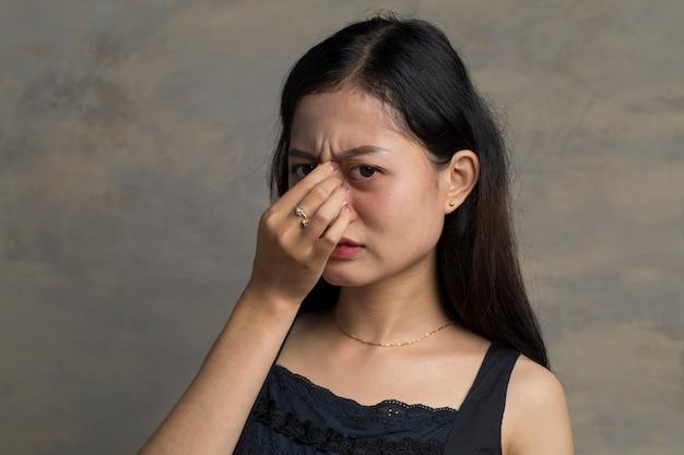 Asiatische frau, die augenschmerzen fühlt