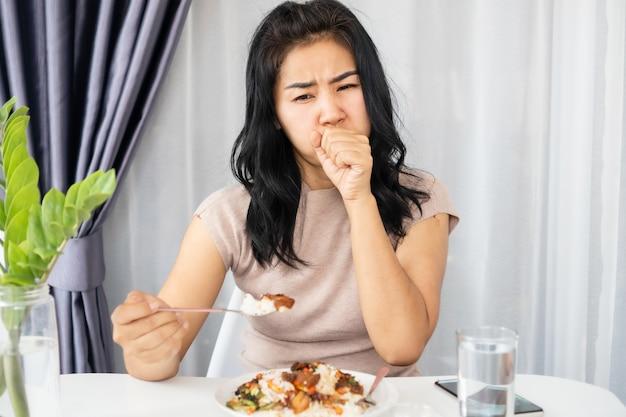 Asiatische frau, die beim essen einer mahlzeit erstickt, versucht sich zu erbrechen oder zu husten