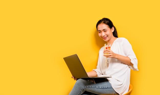 Asiatische frau, die bier trinkt und an seinem laptop arbeitet. und ein glückliches lächeln glückliches arbeitskonzept auf gelbem hintergrund im studio