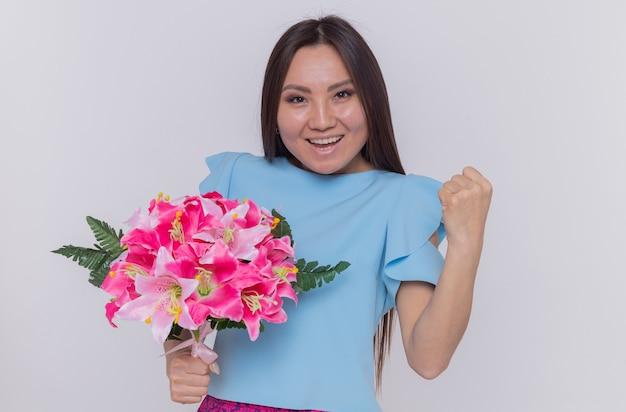 Asiatische frau, die blumenstrauß hält, der glückliche und fröhliche geballte faust sieht, die internationalen frauentag über weißer wand steht