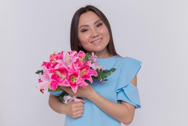 Asiatische frau, die blumenstrauß hält, der glücklichen und fröhlichen internationalen frauentag steht, der über weißer wand steht