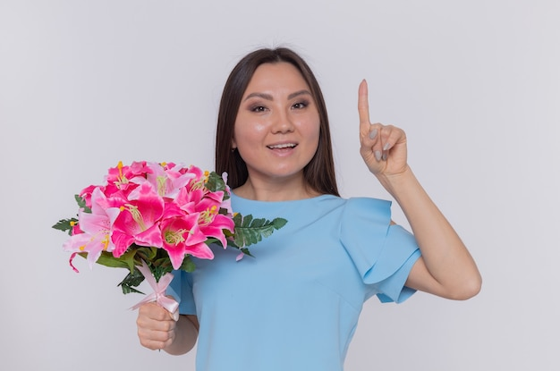Asiatische frau, die blumenstrauß hält, der glückliches und fröhliches lächeln zeigt zeigefinger zeigt internationalen frauentag, der über weißer wand steht