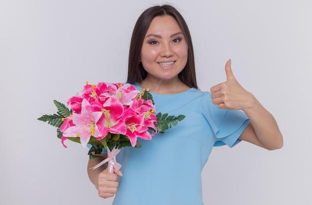 Asiatische frau, die blumenstrauß hält, der glückliches und fröhliches lächeln zeigt, zeigt daumen hoch und feiert internationalen frauentag, der über weißer wand steht