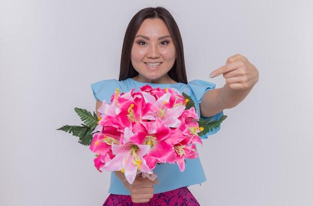 Asiatische frau, die blumenstrauß hält, der mit zeigefinger auf blumen zeigt, die glücklich und fröhlich schauen