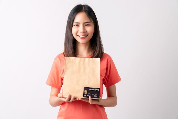 Asiatische frau, die braune leere bastelpapiertüte und kreditkarte auf weißem hintergrund hält.