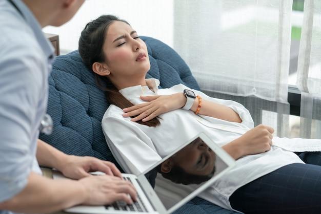 Asiatische frau, die brustschmerzen fühlt, die auf dem sofa liegen, während arzt ihre symptome fragt