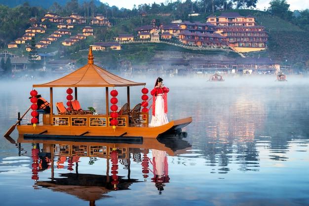 Asiatische frau, die chinesische traditionelle kleidung auf einem boot im ban rak thai-dorf, provinz mae hong son trägt