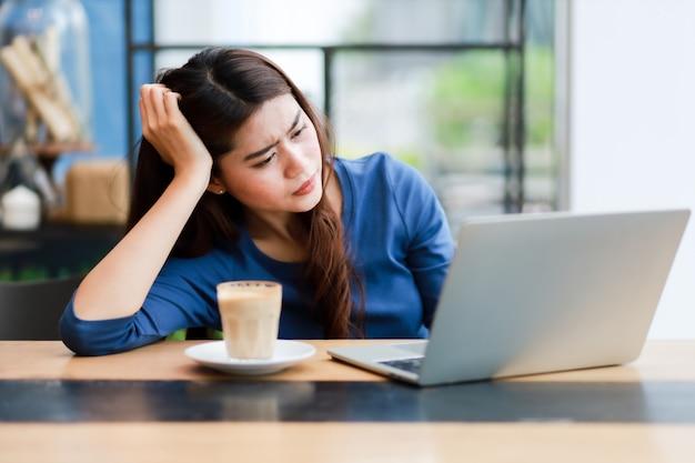 Asiatische frau, die computer-laptop verwendet und kaffeearbeit vom hauptkonzept trinkt