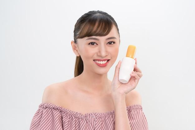 Asiatische frau, die creme auf ihrer hand zeigt, isoliert auf weiß