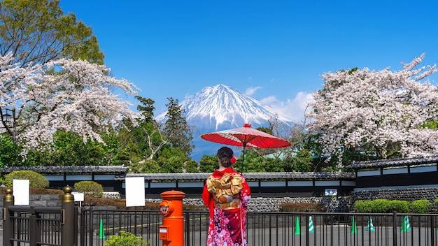 Asiatische frau, die den traditionellen japanischen kimono am fuji-berg und an der kirschblüte im frühjahr fujinomiya in japan trägt.