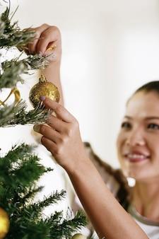Asiatische frau, die den weihnachtsbaum verziert.