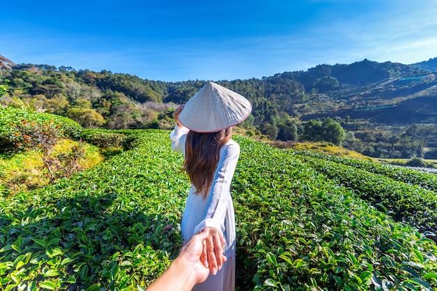 Asiatische frau, die die traditionelle hand des mannes der vietnamkultur trägt und ihn zum grünen teefeld führt.