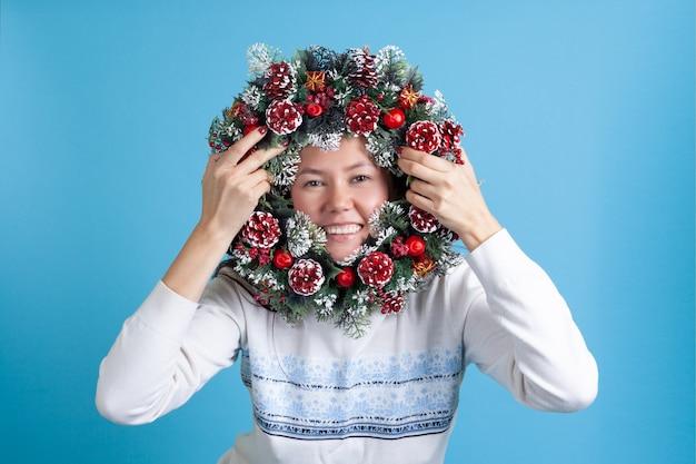 Asiatische frau, die durch einen weihnachtskranz schaut