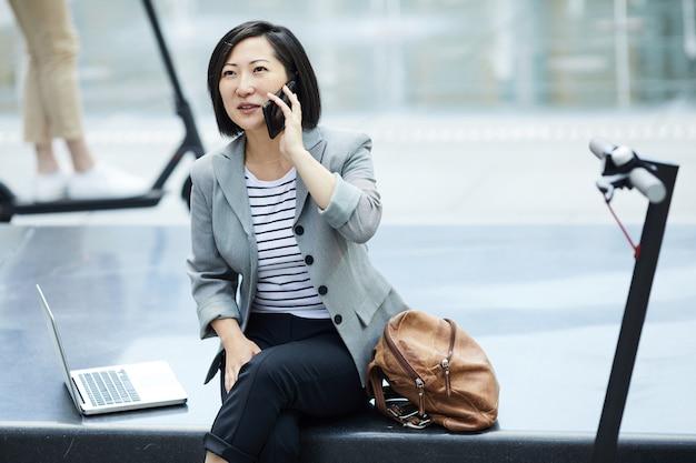 Asiatische frau, die durch smartphone in der stadt spricht