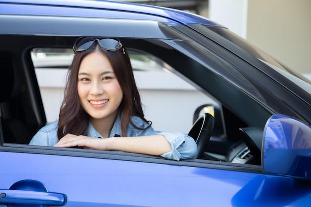 Asiatische frau, die ein auto fährt und glücklich mit freudigem positivem ausdruck während der fahrt zur reise lächelt, genießen leute, transport zu lachen und durch konzept zu fahren