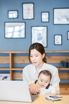 Asiatische frau, die ein baby hält und einen laptop drinnen bedient