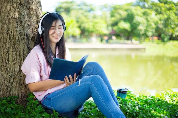 Asiatische frau, die ein buch liest und im park lächeltzufriedene asiatische frau, die ein buch in einem park liest