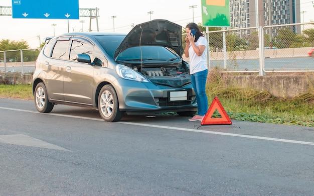 Asiatische frau, die ein handy hält, das um das auto geht. das auto ging kaputt