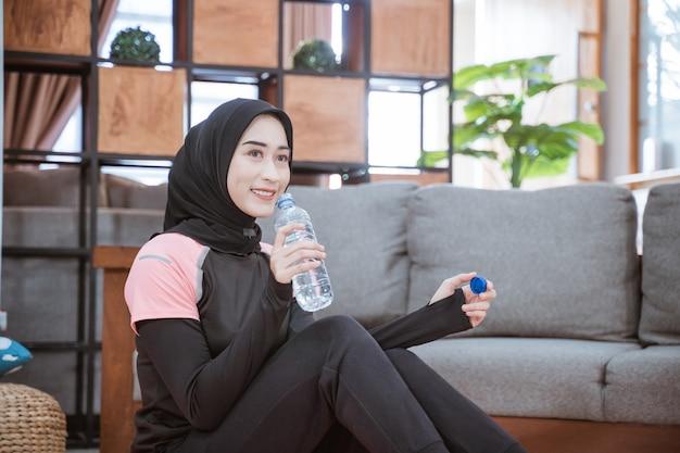 Asiatische frau, die ein hijab-fitness-outfit trägt, sitzt auf dem boden und hält eine trinkwasserflasche im wohnzimmer