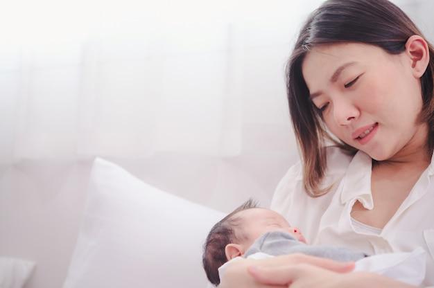 Asiatische frau, die ein neugeborenes baby in ihren armen zu hause hält.