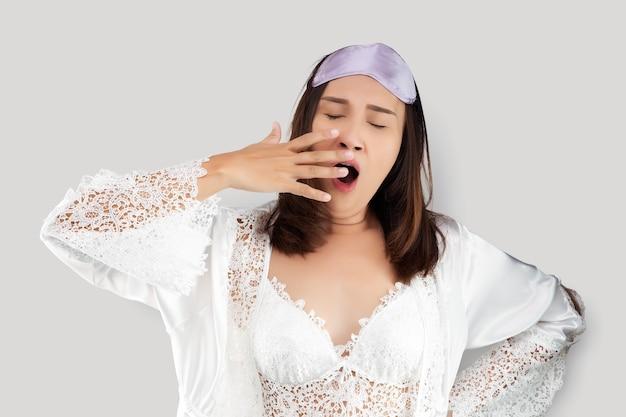 Asiatische frau, die ein weißes nachthemd und ein gähnendes satingewand trägt, die eine schläfrige geste zeigen, die mund mit seiner hand bedeckt.