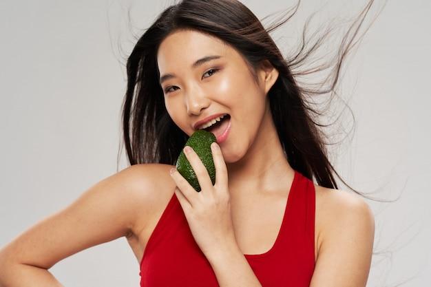 Asiatische frau, die eine avocado hält