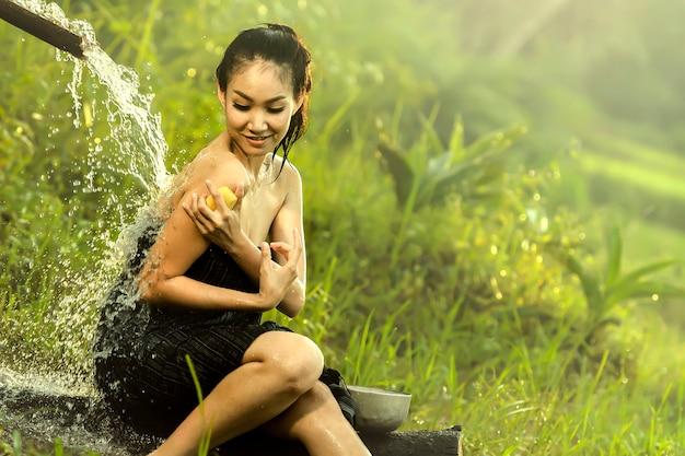 Asiatische frau, die eine dusche nimmt.