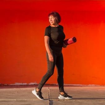 Asiatische frau, die eine fitnessmatte hält